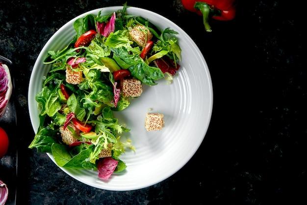 サラダにサーモン、チェリートマト、アボカドを混ぜて、暗い大理石のテーブルの白いプレートに盛り付けます。レストランの食べ物。