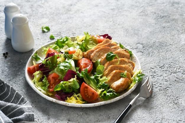 Салат смешать с помидорами и куриным филе в тарелке.