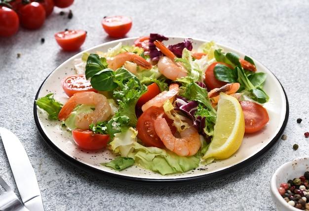 Смешайте салат с помидорами и креветками-гриль с соусом и клематисами на кухонном столе. бетонная поверхность для пищевых продуктов.