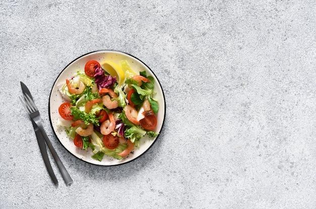 Смешайте салат с помидорами и креветками-гриль с соусом и клематисами на кухонном столе. вид сверху. конкретный пищевой фон.
