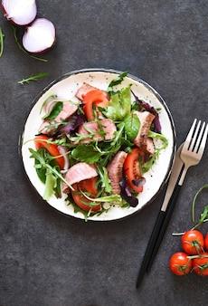 暗い背景のプレートにサラダとトマトとミディアムビーフを混ぜます。