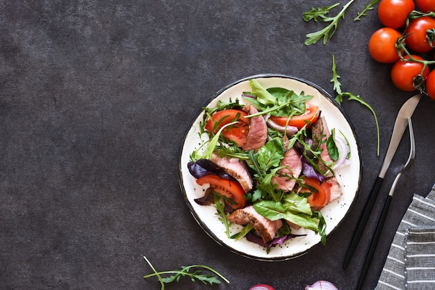 Mix salad with tomatoes and medium beef in a plate on a dark background.