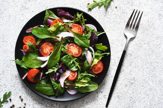 Mix salad with tomatoes, onions and olive oil in a black plate.