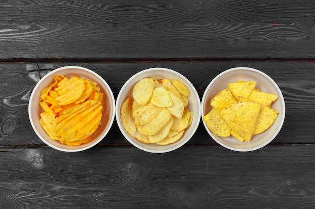 Mix of snacks : pretzels , crackers , chips  and nachos on the table
