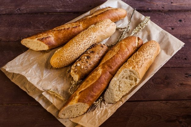 Mix of sorts of baguettes on a wooden table. bakery products.