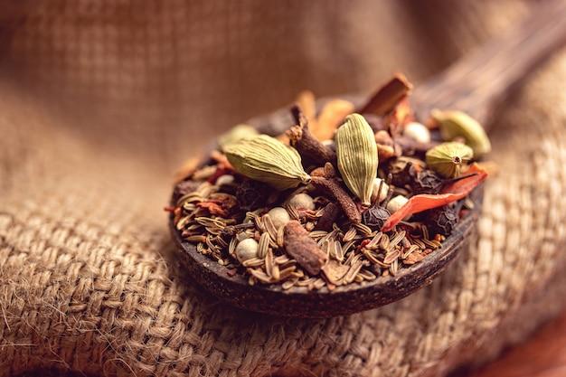 Смешайте специи и травы в деревянной ложке. индийские специи пищевые и кухонные ингредиенты
