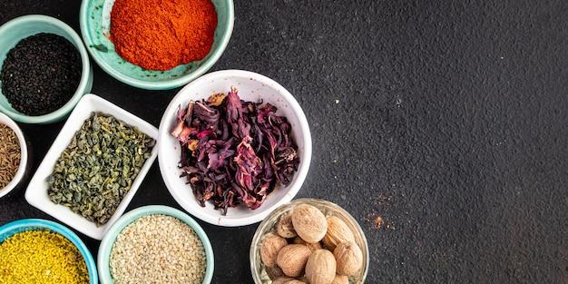テーブルの上でさまざまな種類の刺激的でスパイシーな新鮮なハーブの挽いたスパイスを味付けするスパイスを混ぜる