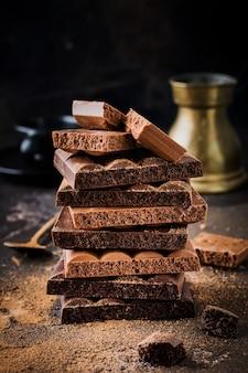 Смешайте стопку горького и молочного пористого воздушного шоколада на темной старой поверхности. выборочный фокус.