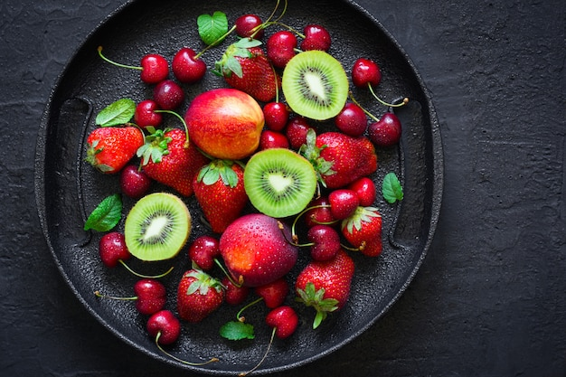 Mix of summer berries and fruits on a black plate.