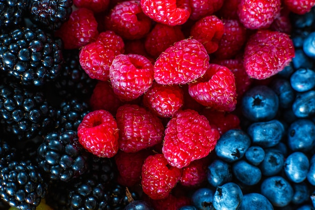 Mix of summer berries vitamins. mulberry, raspberry and blueberry. stylish layout on a black table.