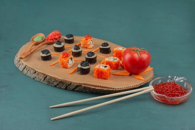 Смешайте суши и красную икру на синей поверхности