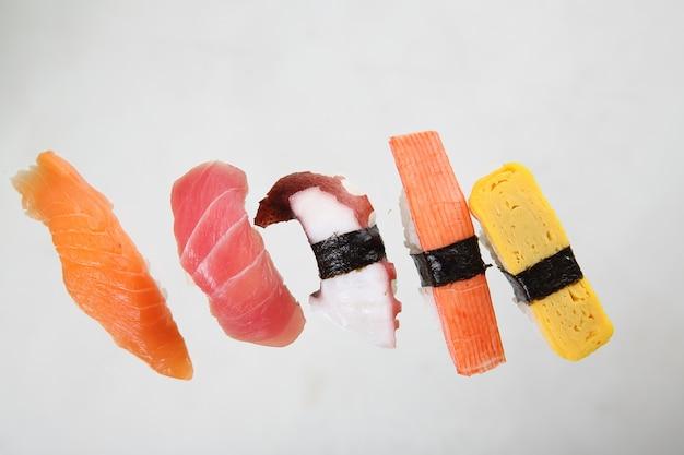 白い背景で隔離の寿司を混ぜる
