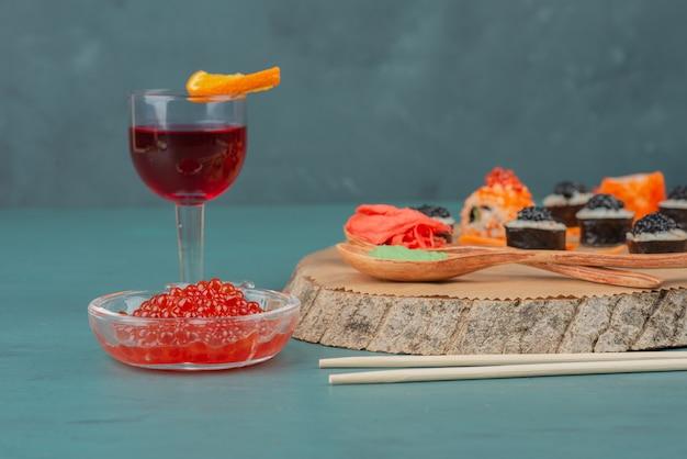 青いテーブルに寿司、赤キャビア、赤ワインを混ぜます。