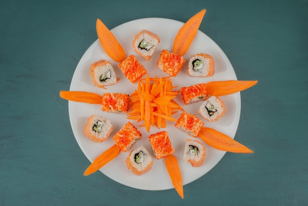 Mix sushi with carrot slices on white plate.