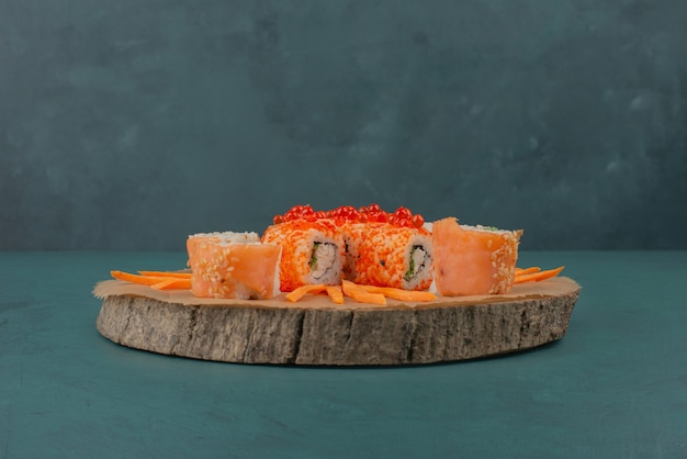 Mix sushi with carrot slices on wooden board.