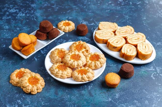 Mix of sweet cookies,cake roll,mini cupcakes.