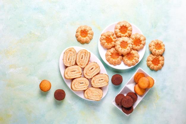Mix di biscotti dolci, rotolo di torta, mini cupcakes.