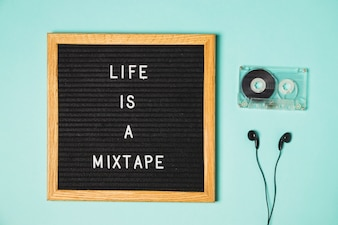 Mix tape message on board with cassette tape and earphone on turquoise backdrop