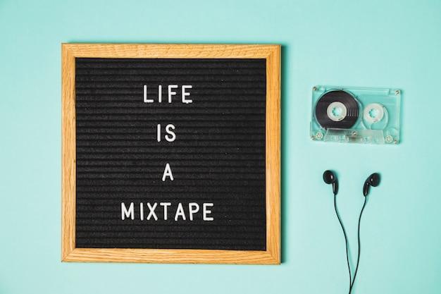 ターコイズブルーの背景にカセットテープとイヤホンを貼ったテープメッセージをミックス