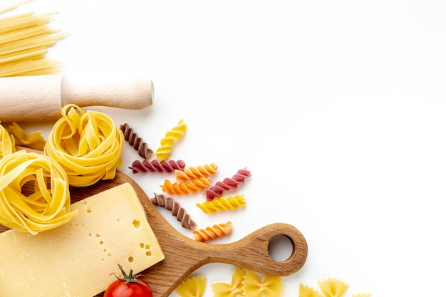 Mix of uncooked pasta and hard cheese with copy space