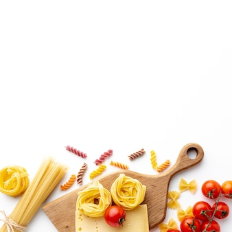 Mix of uncooked pasta tomatoes and hard cheese with copy space