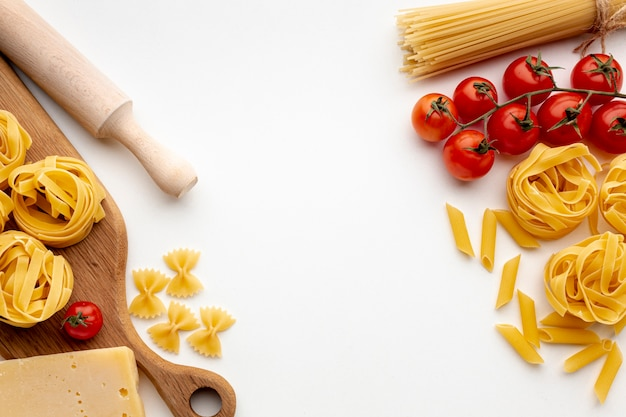 Mix of uncooked pasta with tomatoes and hard cheese