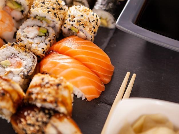 スタジオで黒い石のバックゴーランドにさまざまな巻き寿司を混ぜる