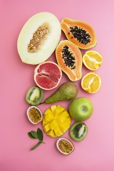 Mix of various exotic fruits. pink background. flat lay.