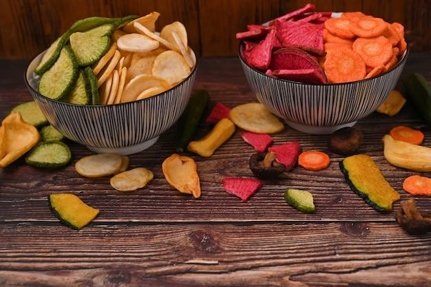 木製のテーブルに野菜のチップスを混ぜます。ビーガンフード。