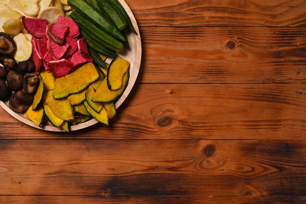 木製のテーブルの上で野菜チップスをオクラ、ニンジン、カボチャ、ビートルート、椎茸と混ぜます。