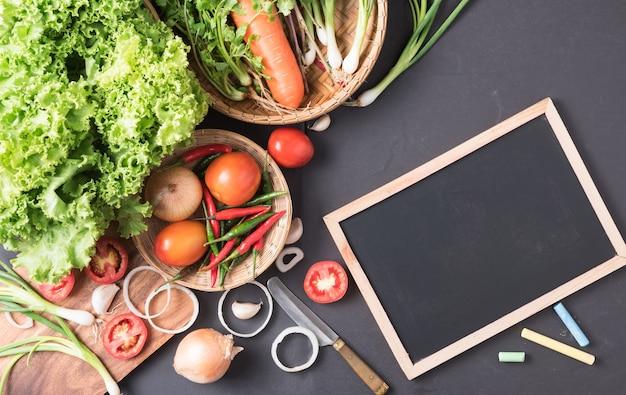 Mix vegetable, salad, tomato, spring onion, coriander, chilli with blackboard on black background, i