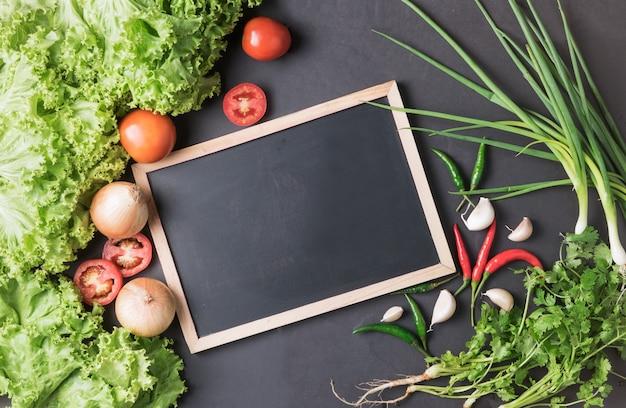 ブラックbcakgroundで黒板と野菜を混ぜる