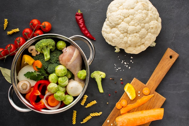 Mix of vegetables and chicken drumstick in pan with carrot on cutting board and cauliflower
