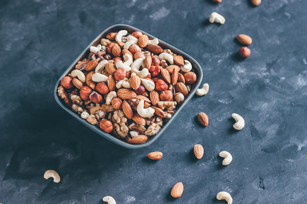 Mix of walnuts, cashews, hazelnuts and almonds in a ceramic bowl on a blue concrete background in dark style