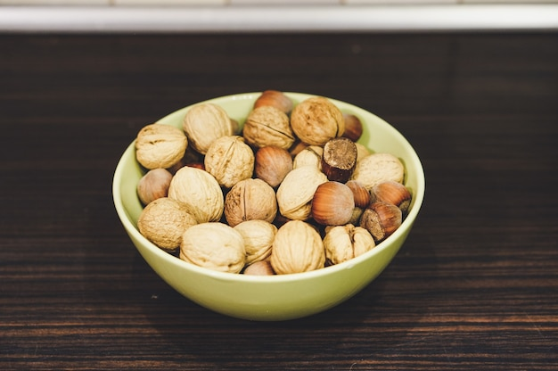 Mix of walnuts and hazelnuts in a yellow bowl on a wooden table