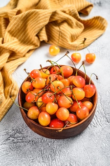 Mix of yellow and red ripe cherries in a bowl. white background. top view.