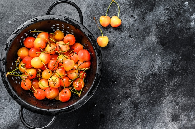 Mix of yellow and red ripe cherries in a colander. black background. top view. copy space.