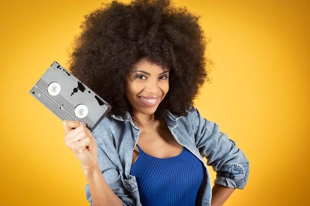 노란색 배경, 복사 공간 손에 복고풍 비디오 테이프로 눈을 덮고 혼합 아프리카 미국 여자