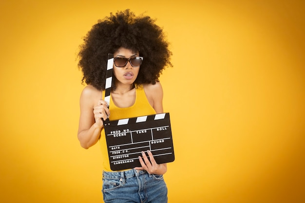 Mixed afro american woman watching movie with a clapperboard and glasses, yellow background