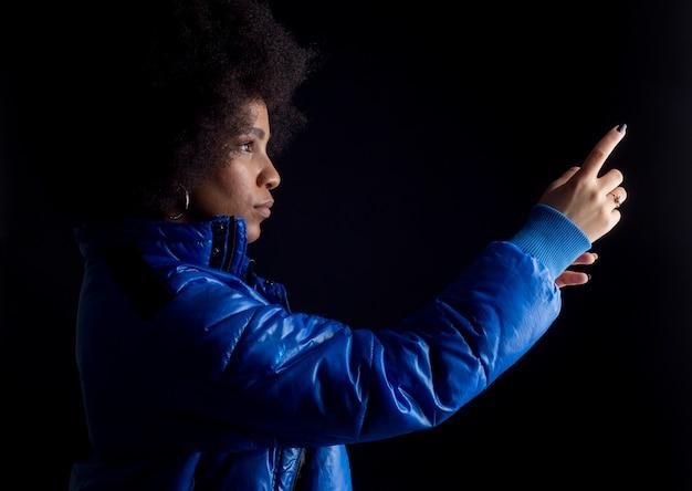 Mixed afro woman posing on dark background urban clothing hip hop music studio recording
