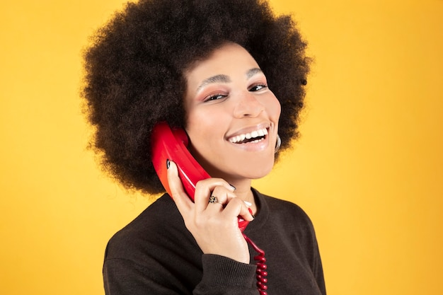 Mixed afro woman, talking on retro red phone, happy smiling