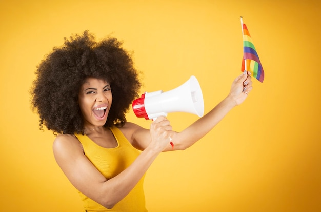 Mixed afro woman with gay pride flag and megaphone, shouts for her rights, on yellow background