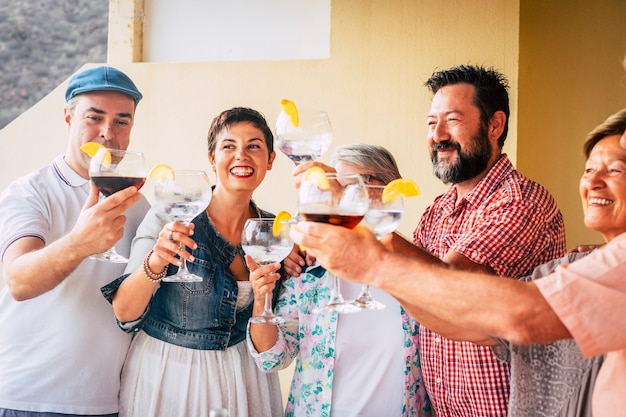 白のウォッカの赤ワインでカクテルを飲むイベントを一緒に祝う、白人の混合年齢のグループ