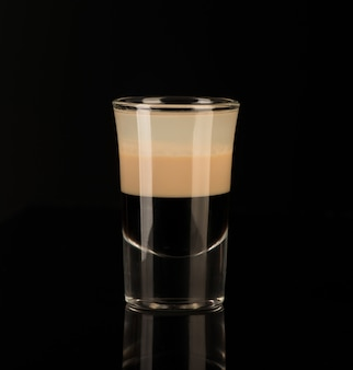 Mixed alcoholic liquor in a shot glass isolated on a black background