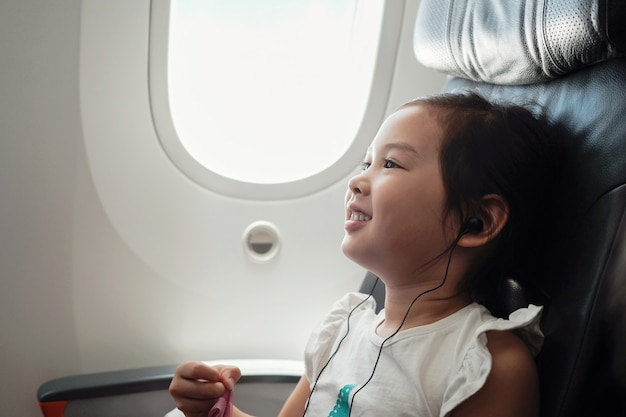 Mixed asian girl watching movie in flight, family traveling abroad with children
