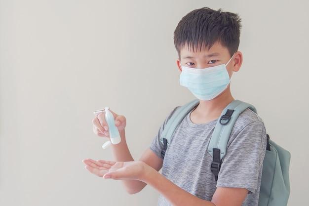 混合アジアプレティーンの少年マスクを着用し、学校のコンセプトに戻って手の消毒剤を適用