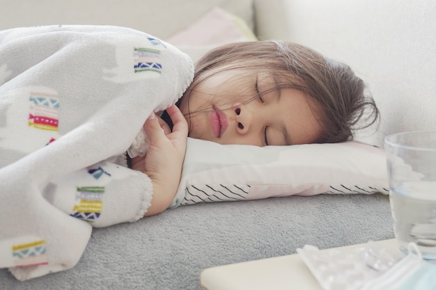 Mixed asian sick girl lying on sofa with chewable pills at home, heath care concept