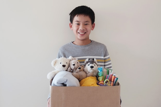 Mixed asian young volunteer preteen teenage boy holding a box full of used toys