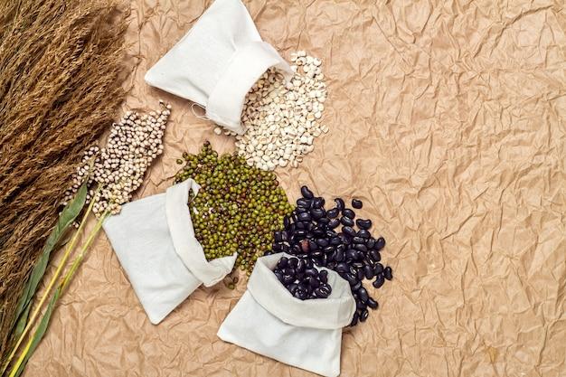 Смешанные бобы в мешок на фоне коричневой бумаги, бобы мунг, соя, черная фасоль, зеленая фасоль, просо