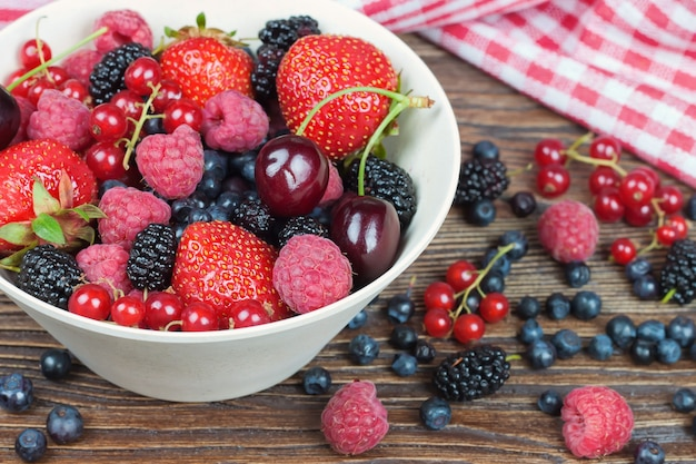 Mixed berries in a bowl on brown wooden table. cherry, strawberry, raspberry, red currant, mulberry, blueberry
